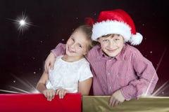Kinderen in Kerstmishoed in huidige dozen Stock Afbeeldingen