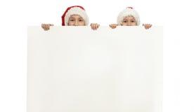 Kinderen in Kerstmishoeden Stock Foto's