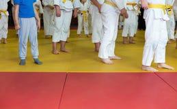 Kinderen in kimono die op tatami op krijgs opwarmen Stock Afbeeldingen