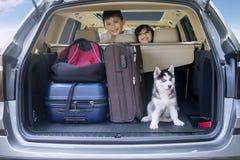 Kinderen klaar voor vakantie met hond in auto Stock Afbeelding