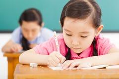 Kinderen in klaslokaal met in hand pen stock afbeeldingen