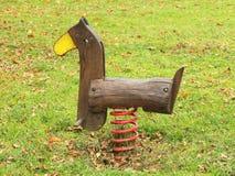 Kinderen kleurrijk houten het slingeren paard in speelplaats Stock Foto's