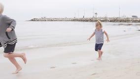 Kinderen langs het strand langs het overzees in werking die worden gesteld die stock videobeelden