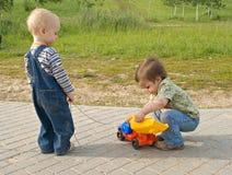 Kinderen met een stuk speelgoed vrachtwagen Stock Afbeelding