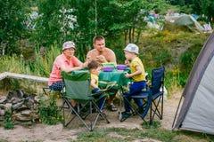 Kinderen met grootmoeder bij een picknick met een tent stock foto