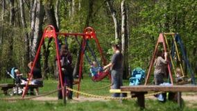 Kinderen met hun moeders, die in het park slingeren stock video