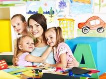Kinderen met leraar op school. stock afbeelding