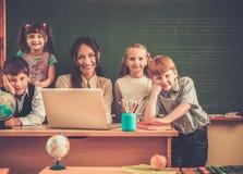 Kinderen met leraar tijdens les in school stock foto