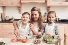 Kinderen met moeder in keuken De moeder helpt jonge geitjes groenten voor salade voorbereiden stock afbeelding