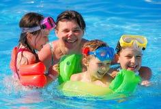 Kinderen met moeder in pool stock foto