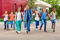 Kinderen met rugzakken dichtbij school het lopen Stock Afbeelding