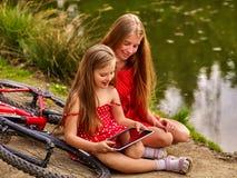 Kinderen met tabletpc dichtbij fiets in rivier in park Royalty-vrije Stock Afbeelding