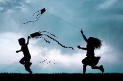 Kinderen met vlieger bij zonsondergang Stock Foto's