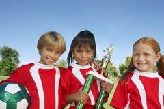 Kinderen met Voetbalbal en Trofee stock fotografie