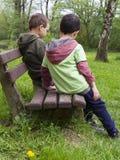 Kinderen op bank in park royalty-vrije stock fotografie