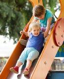 Kinderen op dia bij speelplaats Royalty-vrije Stock Fotografie