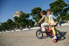 Kinderen op een fiets dichtbij Witte Toren in Thessaloniki Stock Foto