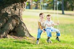 Kinderen op een schommeling op een aard royalty-vrije stock afbeelding