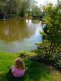 Kinderen op gras door meer stock afbeeldingen