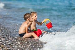 Kinderen op overzees strand Stock Foto's