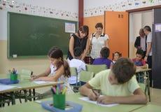 Kinderen op school met leraar stock afbeeldingen