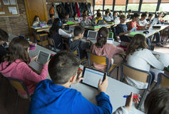 Kinderen op school met tabletten stock foto's