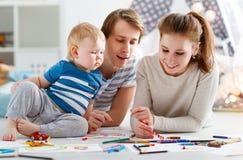 Kinderen` s creativiteit de de gelukkige vader en zoon van de familiemoeder trekken Stock Foto's
