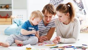 Kinderen` s creativiteit de de gelukkige vader en zoon van de familiemoeder trekken royalty-vrije stock afbeelding