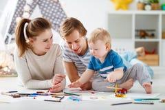 Kinderen` s creativiteit de de gelukkige vader en zoon van de familiemoeder trekken Royalty-vrije Stock Foto's