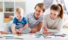 Kinderen` s creativiteit de de gelukkige vader en zoon van de familiemoeder trekken stock afbeeldingen