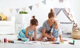 Kinderen` s creativiteit de moeder en de kinderen trekken verven in spel stock afbeeldingen