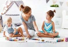 Kinderen` s creativiteit de moeder en de kinderen trekken verven in spel stock fotografie