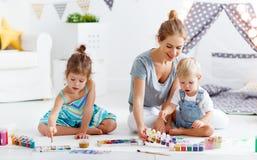 Kinderen` s creativiteit de moeder en de kinderen trekken verven in spel royalty-vrije stock afbeeldingen