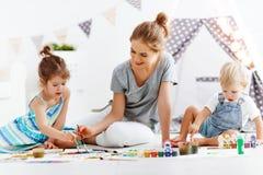 Kinderen` s creativiteit de moeder en de kinderen trekken verven in spel stock foto