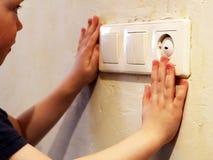 Kinderen` s hand die gevaar van een elektrostroom symboliseren stock foto