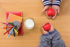 Kinderen` s handen rood hart en notitieboekje met kleurenpotlood houden en melk die op houten Engelse lijst Royalty-vrije Stock Foto's