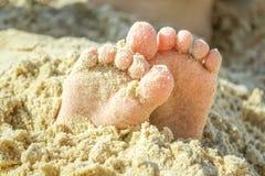 Kinderen` s hielen in zand stock afbeelding