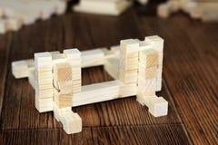 Kinderen` s houten blokken, die een huis bouwen stock foto's