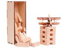 Kinderen` s houten die blokken bovenop elkaar, met een modeldievliegtuig worden gestapeld, op witte achtergrond wordt geïsoleerd Royalty-vrije Stock Afbeeldingen