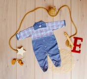 Kinderen` s kleding met speelgoed op een houten achtergrond royalty-vrije stock foto