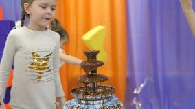 Kinderen` s speelkamer De kinderen eten chocolade van een chocoladefontein stock footage