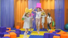 Kinderen` s speelkamer De meisjes vervuilen met zacht speelgoed stock videobeelden