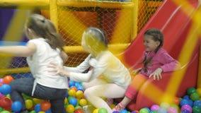 Kinderen` s speelkamer De kinderen spelen in een droog bassin dat met plastiek gekleurde ballen wordt gevuld stock videobeelden