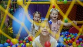 Kinderen` s speelkamer De kinderen spelen in een droog bassin dat met plastiek gekleurde ballen wordt gevuld stock video