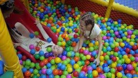 Kinderen` s speelkamer De kinderen spelen in een droog bassin dat met plastiek gekleurde ballen wordt gevuld stock footage