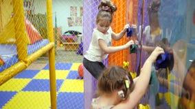 Kinderen` s speelkamer Het kind beklimt de muur van een het beklimmen muur stock videobeelden