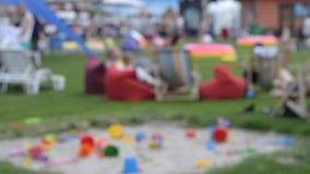 Kinderen` s speelplaats met zand en zetelzakken op groen gras stock videobeelden