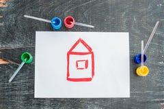 Kinderen` s tekening van een huis met gekleurde verven wordt geschilderd die Het concept van het huis Royalty-vrije Stock Foto's