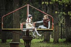 Kinderen` s vreugde op de carrousel Stock Foto's