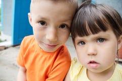 Kinderen selfie portretten die voor huis zitten Gelukkige jonge geitjes Kaukasische Russische siblings samen Jonge geitjes selfie stock fotografie